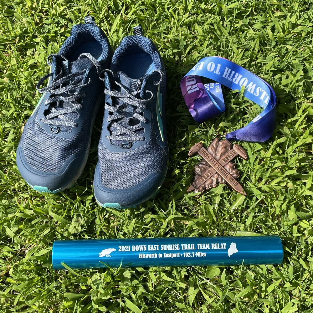 My trail runners, medal and the team's relay baton.